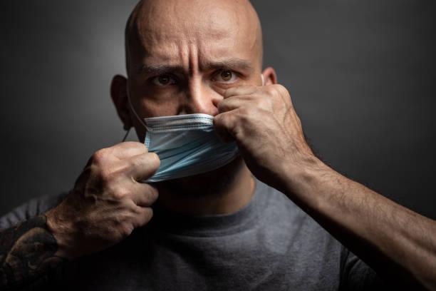 de mens scheurt een beschermend masker van zijn gezicht. - tears corona stockfoto's en -beelden