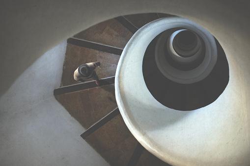 man rising surreal spiral stairs