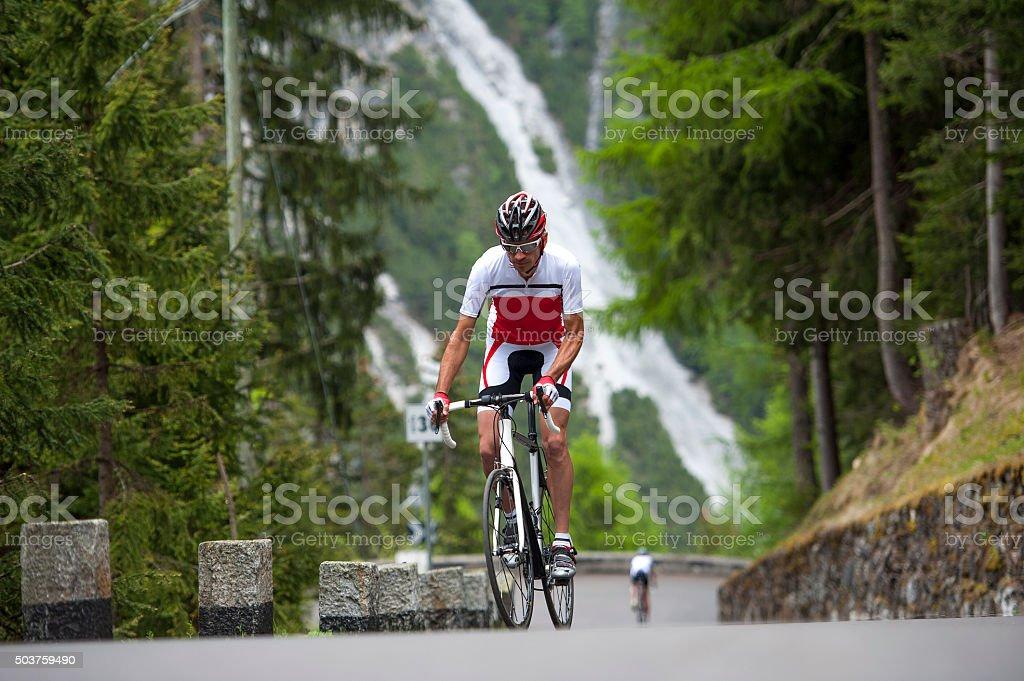 man roadcycling uphill - bike uphill stock photo