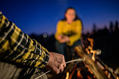 Close up of man's hand roasting marshmallow over campfire at dusk.