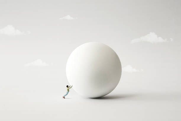 man rolling big heavy ball, surreal concept stock photo