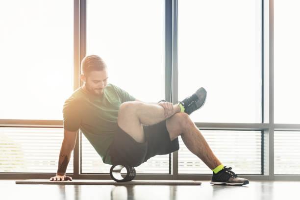hombre rollos sus dildos delante de una ventana - atleta papel social fotografías e imágenes de stock