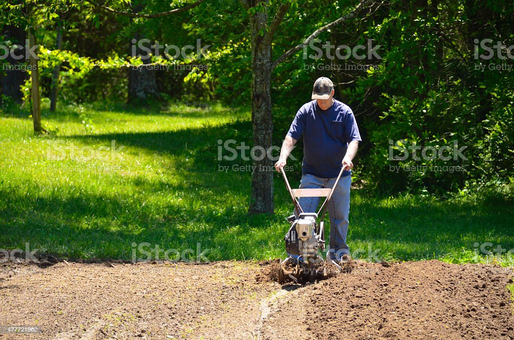 Man rototilling garden stock photo