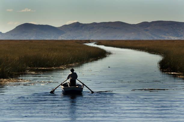 男性の手漕ぎボートの湖チチカカ川、南アメリカ、ペルー共和国 - チチカカ湖 ストックフォトと画像