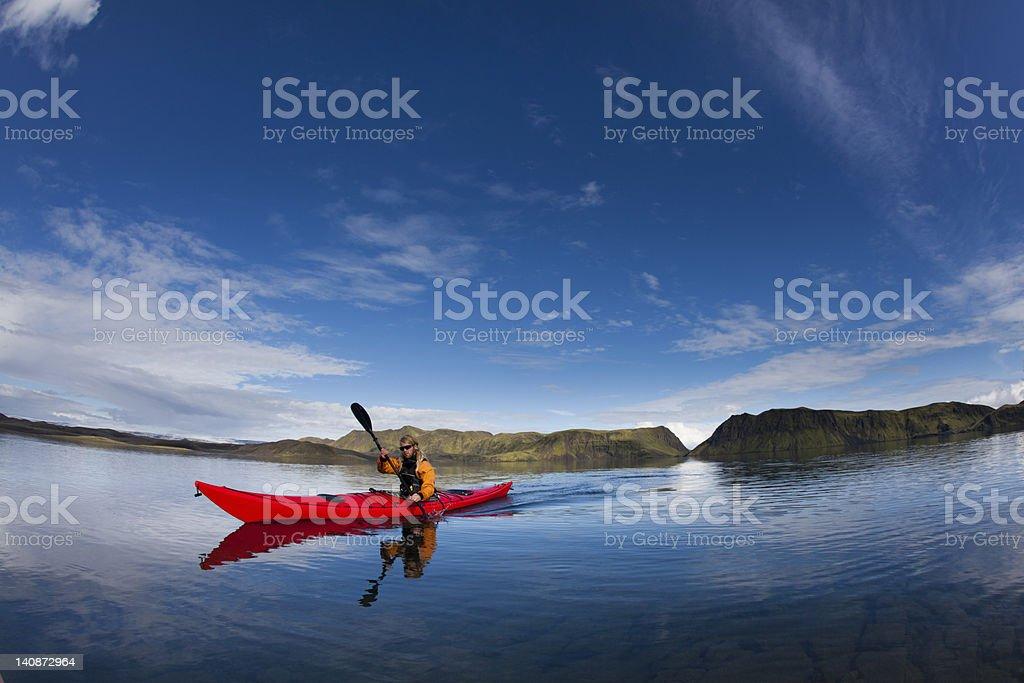 Man rowing canoe in still lake stock photo