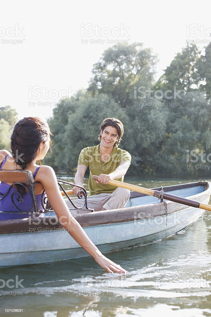 Man rowing girlfriend in rowboat on lake royalty-free stock photo
