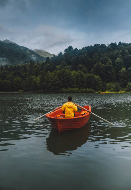 A man rowing in a boat enjoying the early morning over the Black Lake, Borçka ,Artvin, Turkey stock photo