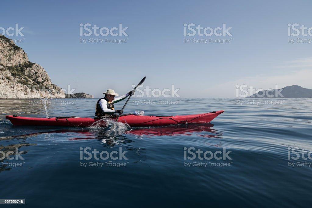 A man rowing on a sea kayak stock photo