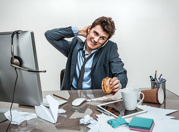 man rubbing his neck with hand at working place - dawdle stock pictures, royalty-free photos & images