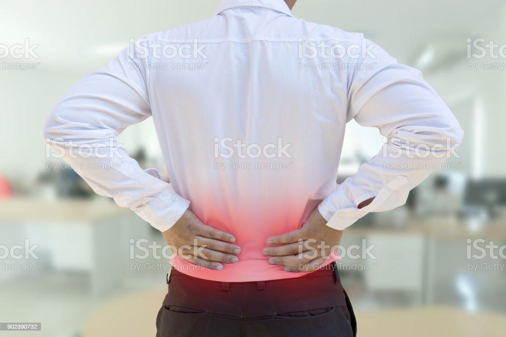 Mann seinem schmerzhaften Rücken reiben. Bürokonzept-Syndrom. – Foto