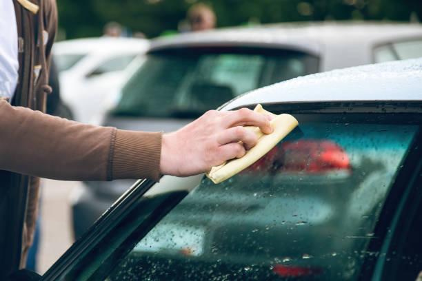 A man rubs a car windshield with a napkin. close-up. stock photo