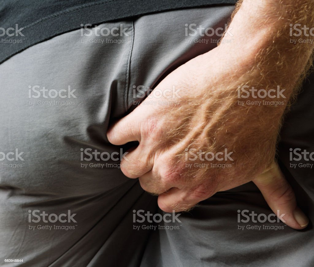 Man rudely scratching his butt through his trousers - foto stock