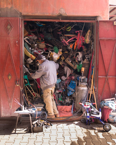 A man rummages through all the objects in a completely full storage room in the medina of Marrakesh stock photo