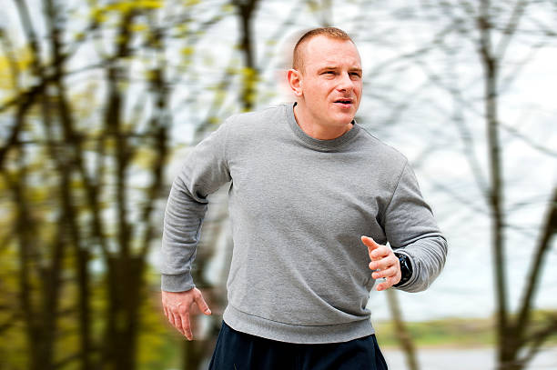 Man run by the river. Outdoor jogger. Blured background. stock photo