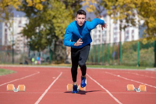 corredor de hombre en camisa azul y pantalones cortos y calzado deportivo en posición estable antes de ejecutar en inicio de carrera. - set deportivo fotografías e imágenes de stock