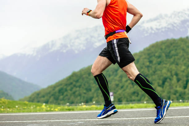 man runner in compression socks stock photo