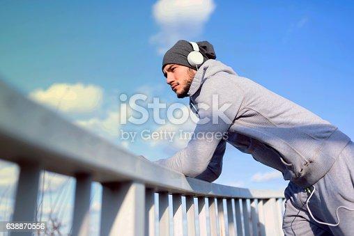 917307226 istock photo Man runner listening music on his smart phone 638870556