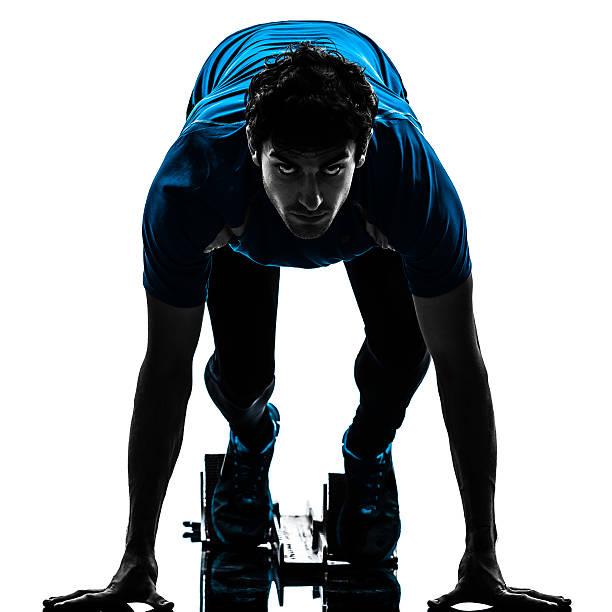 homme de coureur sur les starting-blocks silhouette sprinter - starting block photos et images de collection