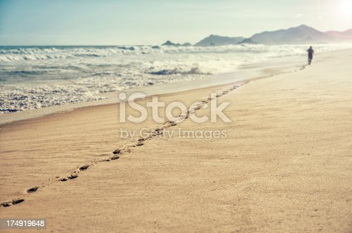 istock Man running along beach left with a long line of footprints 174919648
