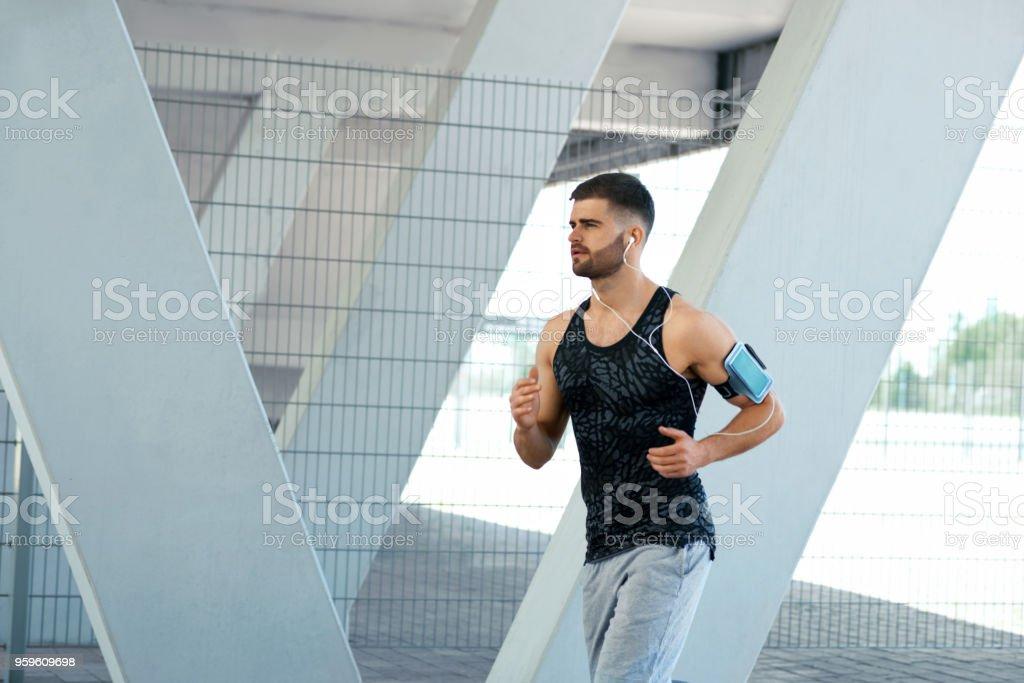 Hombre correr y escuchar música en la calle - Foto de stock de A la moda libre de derechos