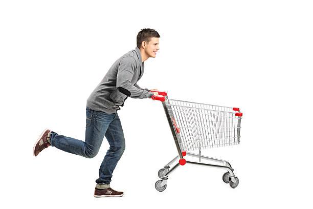 Man running and pushing an empty cart stock photo