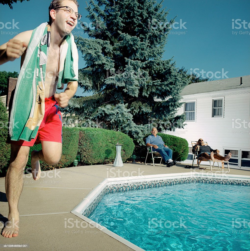 Man running around pool, smiling royalty-free stock photo