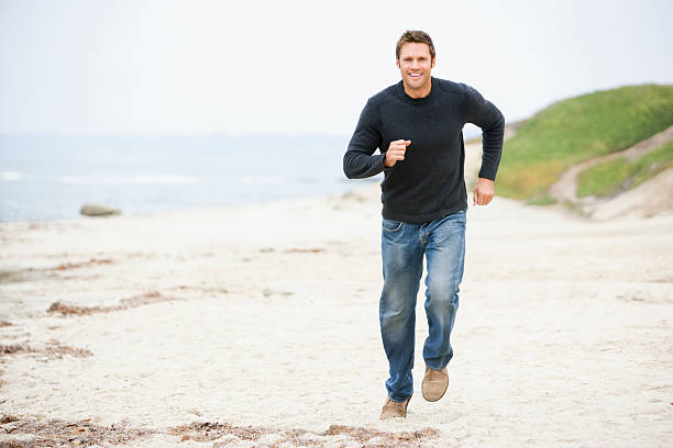 homme jogging sur la plage souriant - près de photos et images de collection