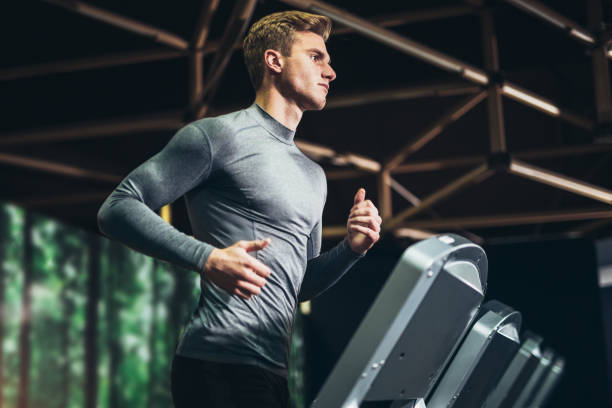 man running at the gym - health club stock photos and pictures