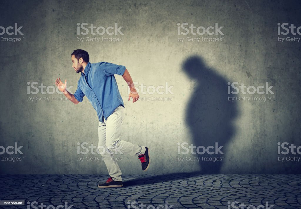 Man running away from his sad gloomy fat shadow on the wall photo libre de droits