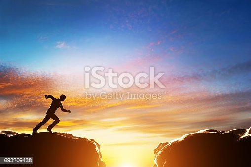 istock Man running fast to jump over precipice between two mountains. Challenge 693209438