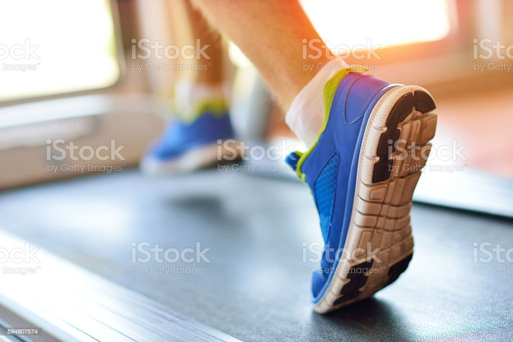 Man running in a gym on a treadmill stock photo