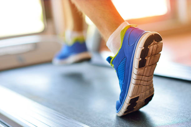 man running in a gym on a treadmill - treadmill stock photos and pictures