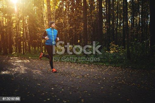 Man running in forest on sunrise. Bright sun glow in upper left corner.