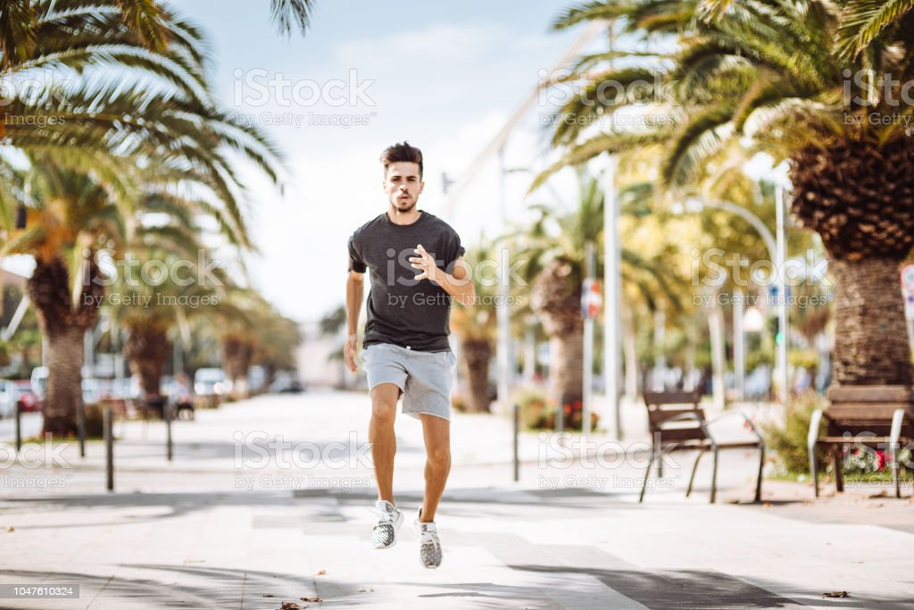 man running in the city streets during the day stock photo