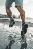 A man is running in the rain, stepping in a large puddle of water. Close-up shot of the feet in water.