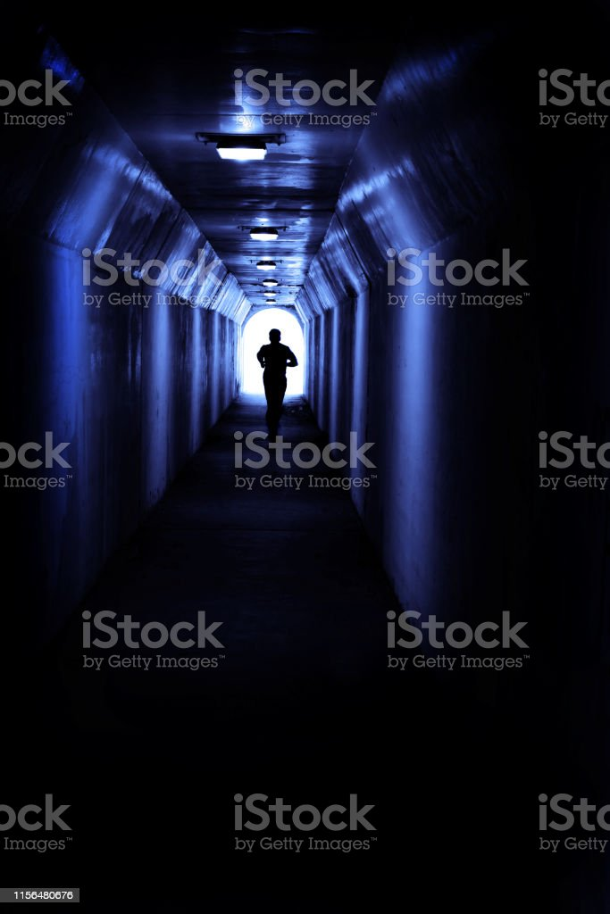 Man running in tunnel towards light seeking a certain destination and...