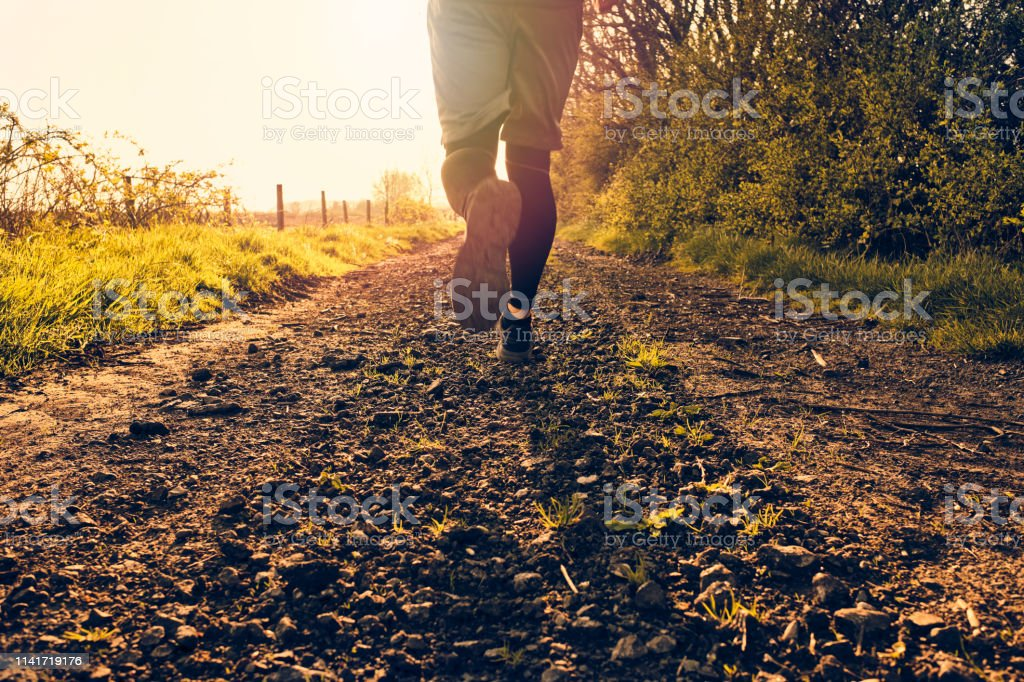 Man running in warm backlit sunshine along a country dirt track. stock photo