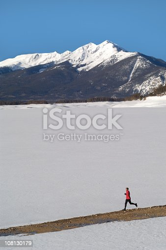 Man Running On Trail Against Snow Covered Mountains