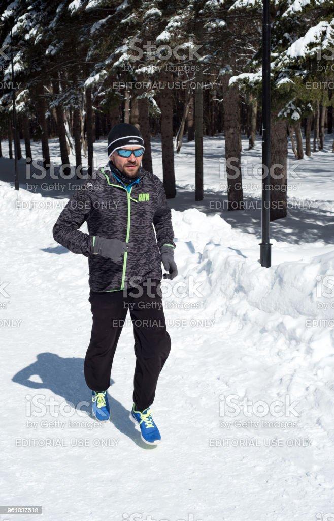 冬の森の雪の中ジョギングを走っている人 - ジョギングのロイヤリティフリーストックフォト