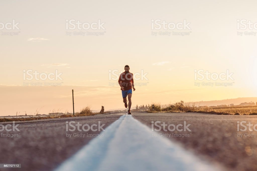 Man running on a paved road stock photo