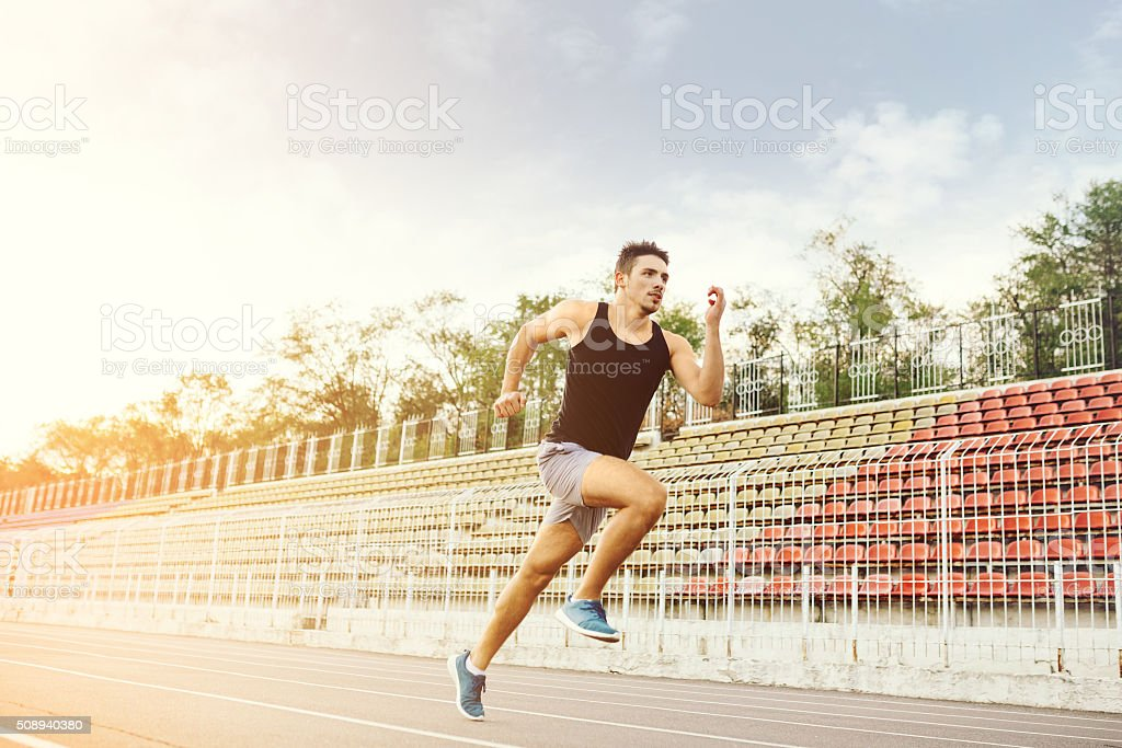 Man running on a racing track stock photo