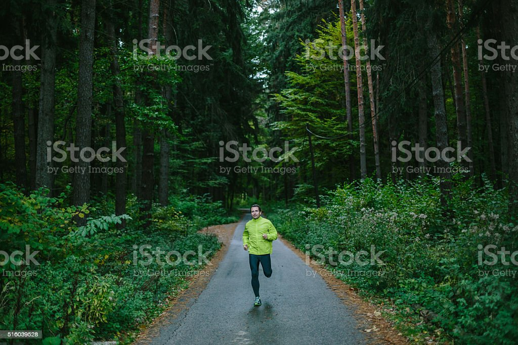 Man running on path in an old green forest. stock photo