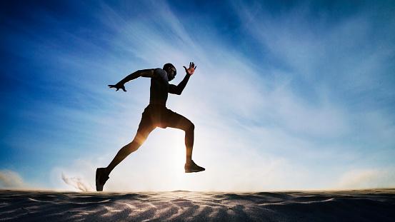 Man running on sand dunes.