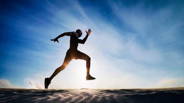 Man running on sand dunes. stock photo