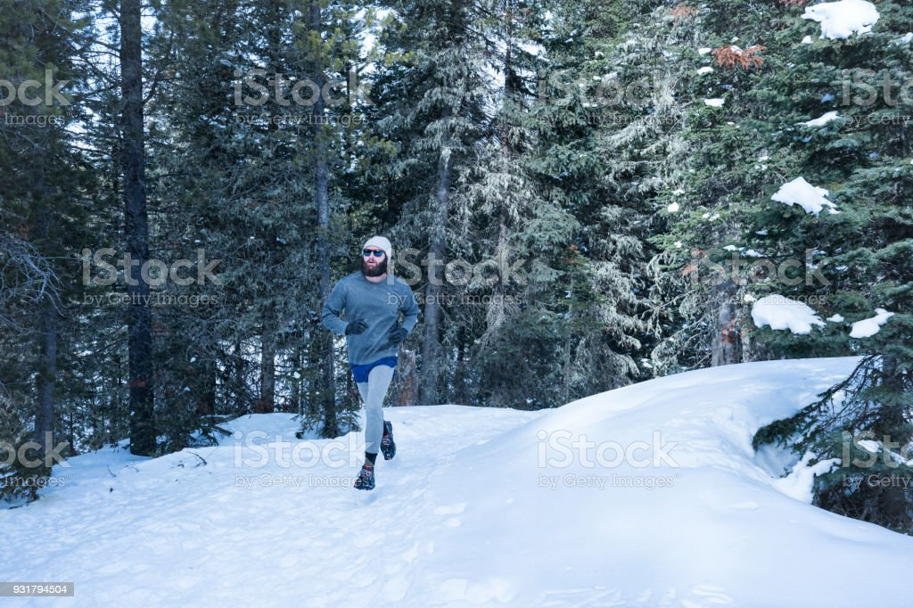 Man running on snowy trails in forest stock photo
