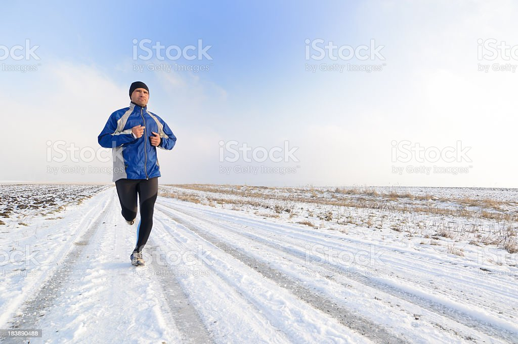 Man running on snowy winter road royalty-free stock photo