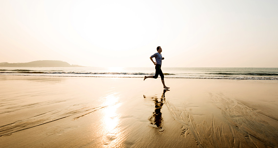 Man running on the beach at sunset.