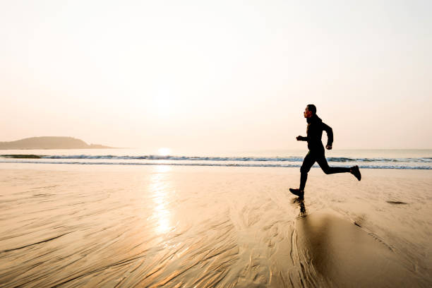 Man running on the beach at sunset stock photo