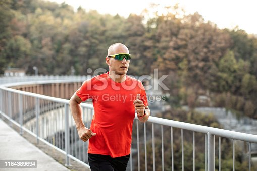 Athlete man running over the bridge just before sunset. He is healthy young professional sportsman.