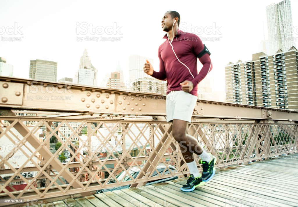 Man running on the brooklyn bridge stock photo